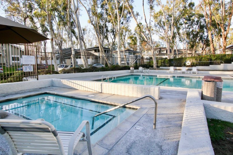 A gated pool and hot tub of Coyote Hills Bluffs with trees and bushes.