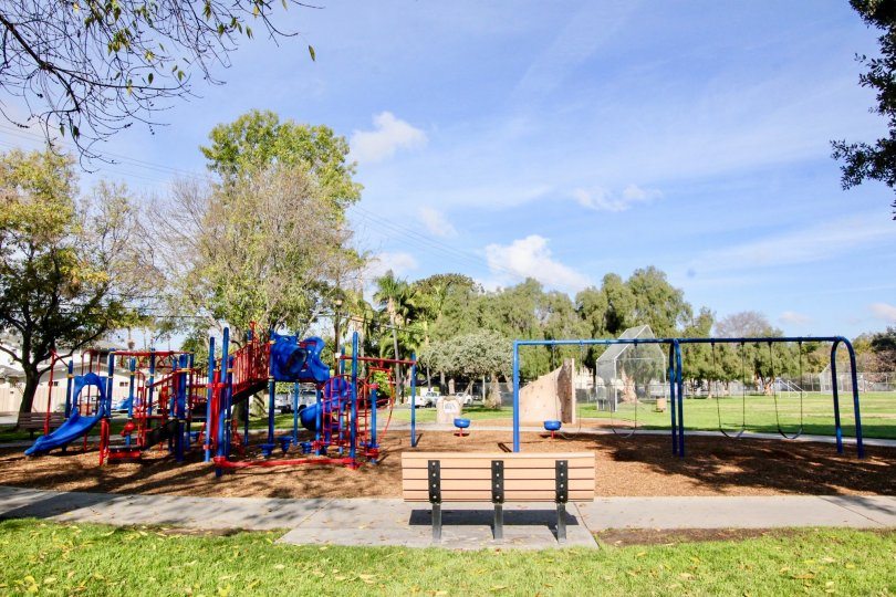 Park in Fullerton Fountains with a bench and a playground on a sunny day.