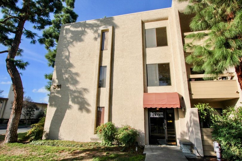 A apartment building in Fullerton Fountains with a door and walkway on a sunny day.