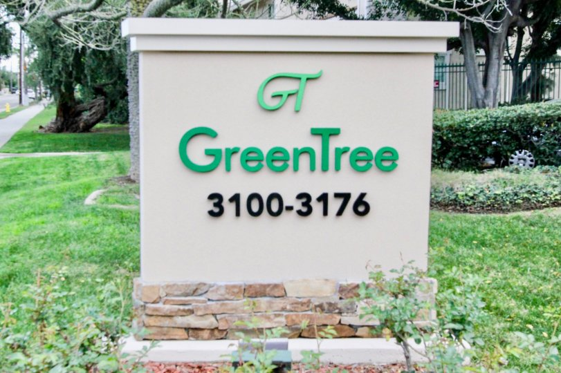 A cement welcome sign with brick base in Green Tree Fullerton, CA