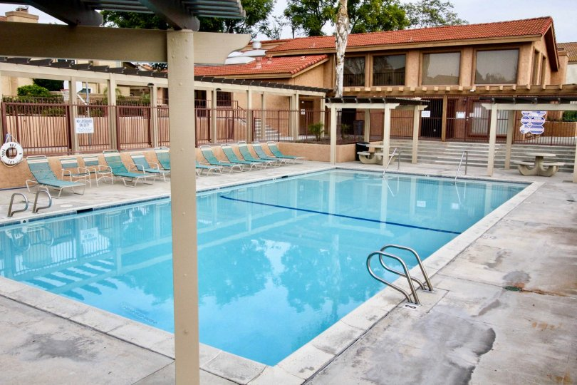 Mark III Townhomes Fullerton California brown colored buildings and blue color pool, chairs looks good