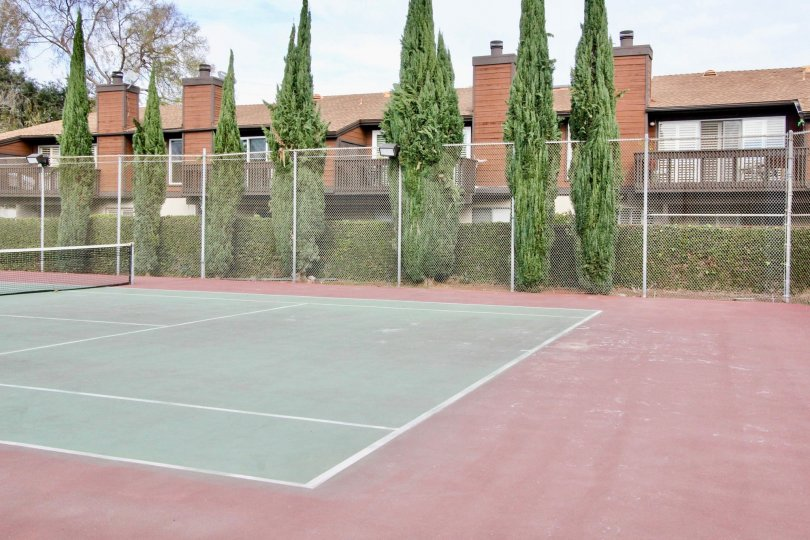 Tennis courts in the Mark III Townhomes with a metal fence on a cloudy day.