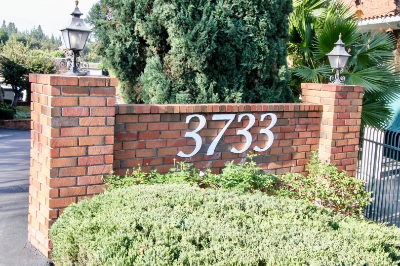 Monarch Manor Fullerton California with brick stone design at front gate and light on the side