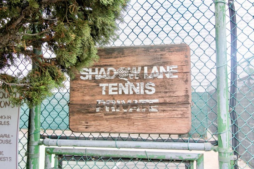 A wooden sign sits against a metal fence at Shadow Lane in Fullerton CA