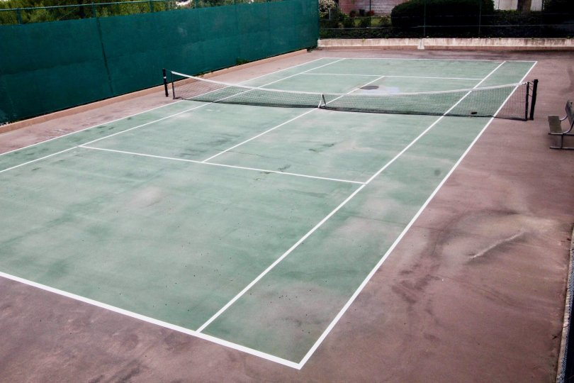 Tennis court is empty, there is no member in it with net and chairs