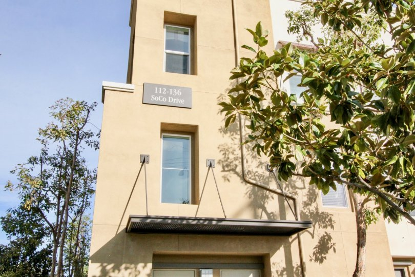 A tall tan building with 112-136 soco drive address on it at soco walk community in fullerton, california.