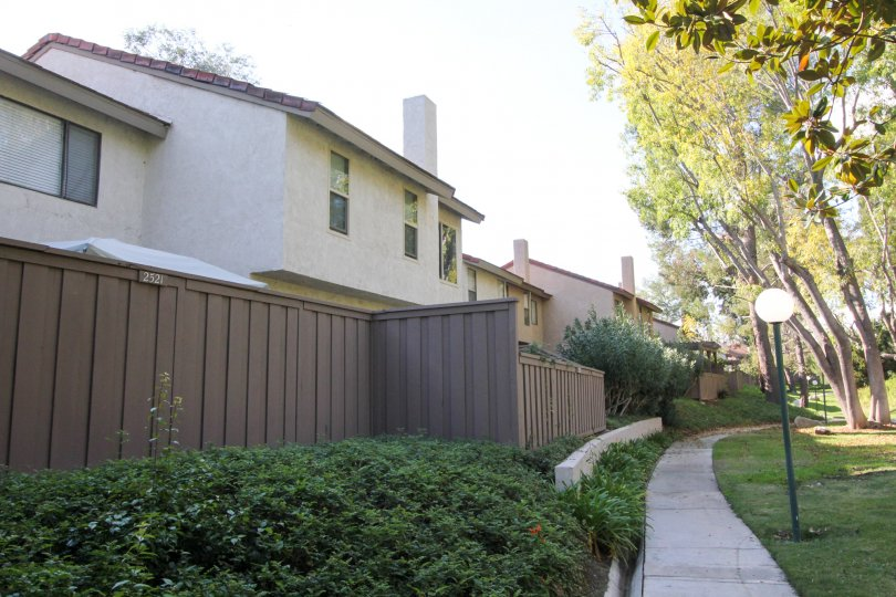 Sidewalk around the Sunny Ridge Townhomes with a fence and lamp posts.