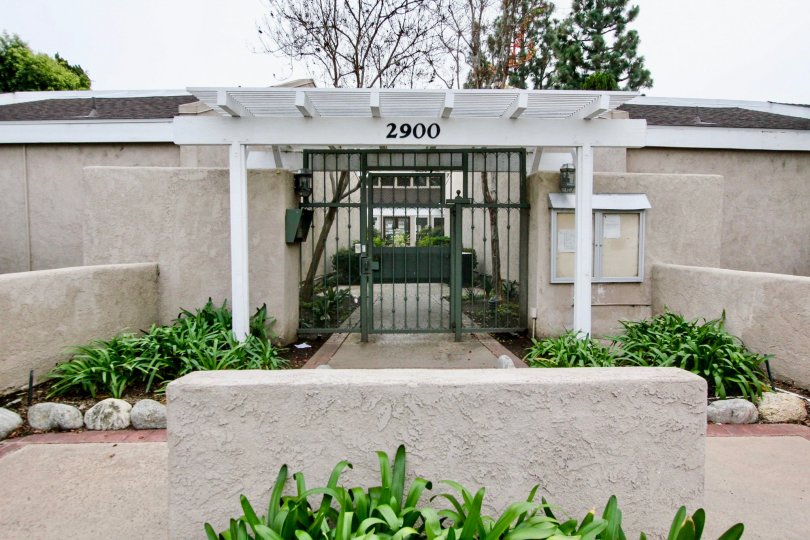 White and black gate with plants along the walls in the arbor community in fullerton, california.
