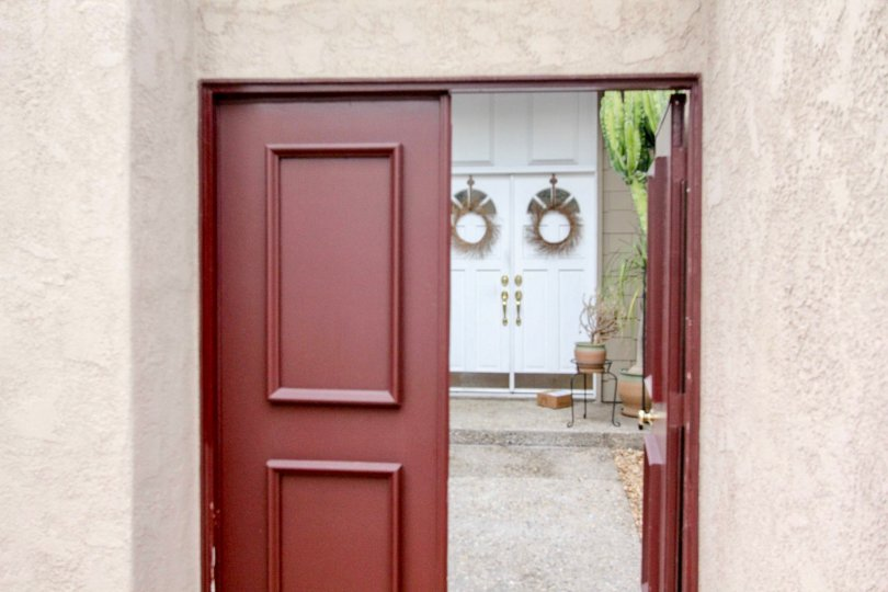 A open red door to The Arbor with potted plants inside.