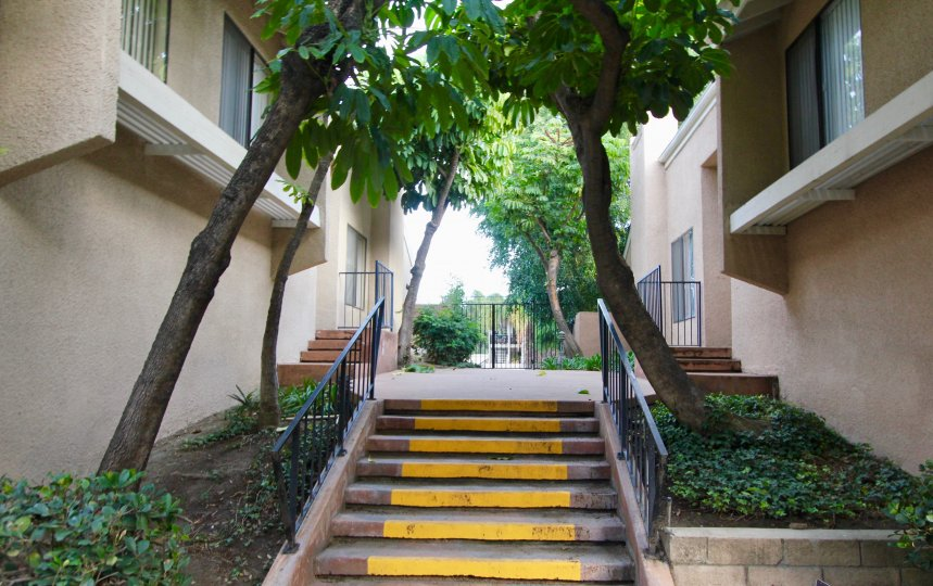 A short set of stairs with yellow stripes painted across each step in Water Gardens in Fullerton CA
