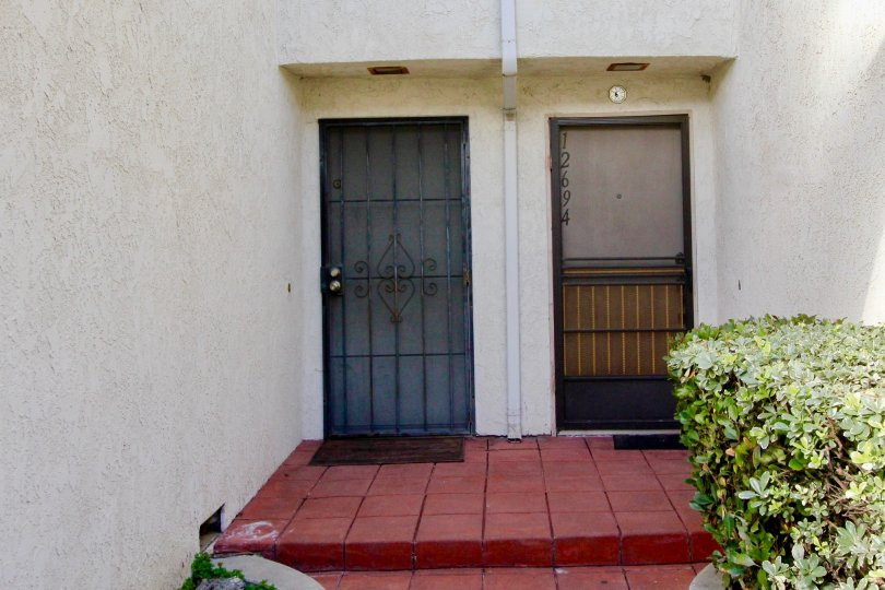 THIS IS THE FRONTWAY TO THE HOME WHICH IS LOCATED IN THE CITY OF GARDEN GROVE THAT LOOKS THE NUMBERS ON THE DOOR AND PLANTS ARE PLANTED