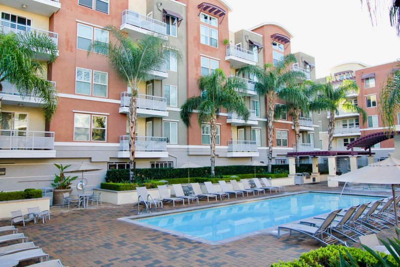 A large swimming pool surrounded by lawn chairs sitting below tall residential buildings at Chapman Commons in Garden Grove CA