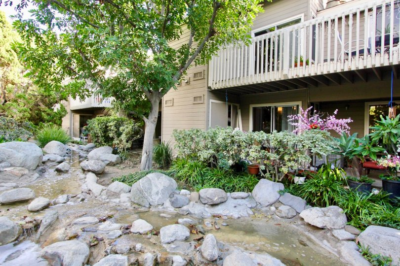 The sun is out at the Cobblestone Creek in Garden Grove, California where the creek is flowing through rocks.