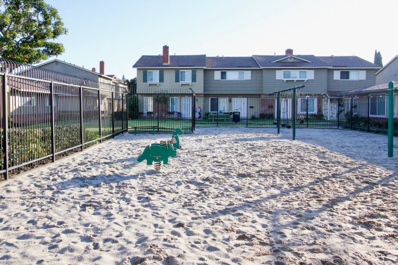 A beautiful gated community that has a sand covered and cozy playground for the children as well.