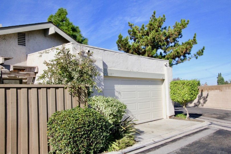 garage view of a house with brown fence on the sire and bushes around
