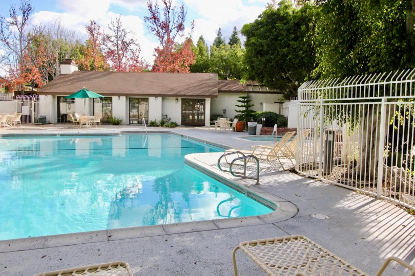 THIS BEAUTIFUL SWIMMING POOL IS IN THE CITY OF GARDEN GROVE THAT THE LOT OF CHAIRS, SHOWS THE LOT OF TREES, NEARBY THE HOME