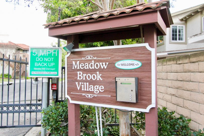 Building at the Meadow Brook Village in Garden Grove with a board and bushes