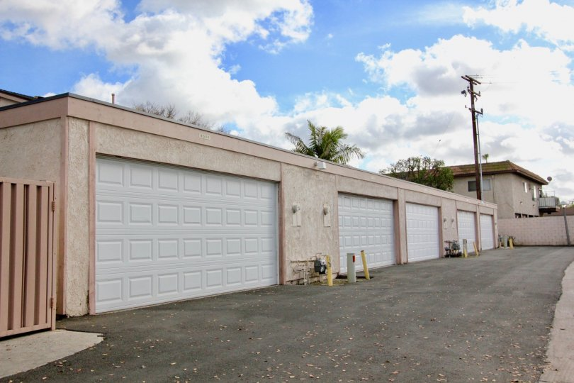 A run down road in an alleyway lined with clean looking garages at New Brookdale in Garden Grove CA