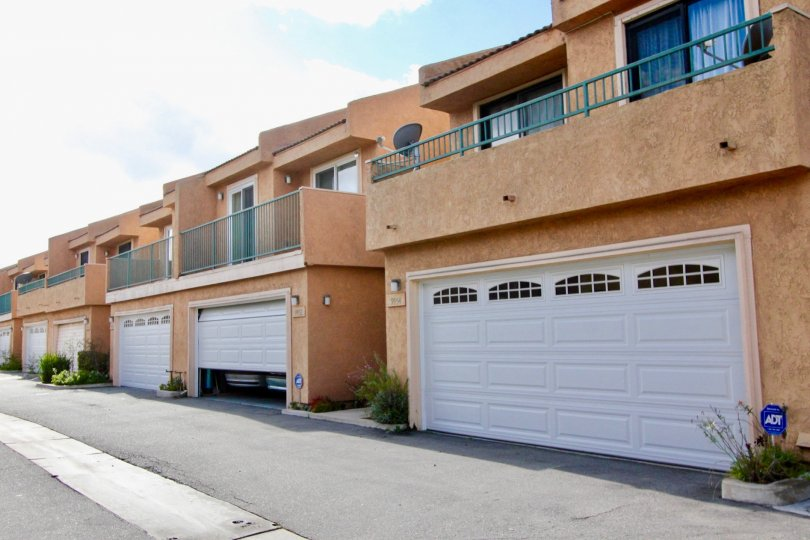 A row of brown condos with garages near a driveway at Park Villas II in Garden Grove CA