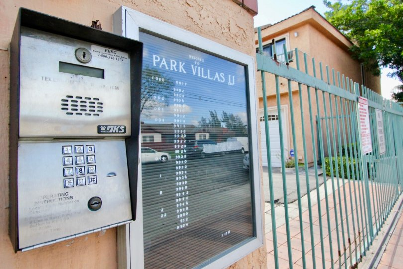 THE BUILDING IN THE PARK VILLAS II WITH THE ELECTRONIC MACHINE, GATE, PLANTS