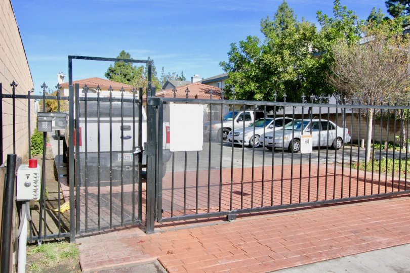 A gated parking lot with a handful of spaces for homeowners in the Pine Villas neighborhood of Garden Grove, California.