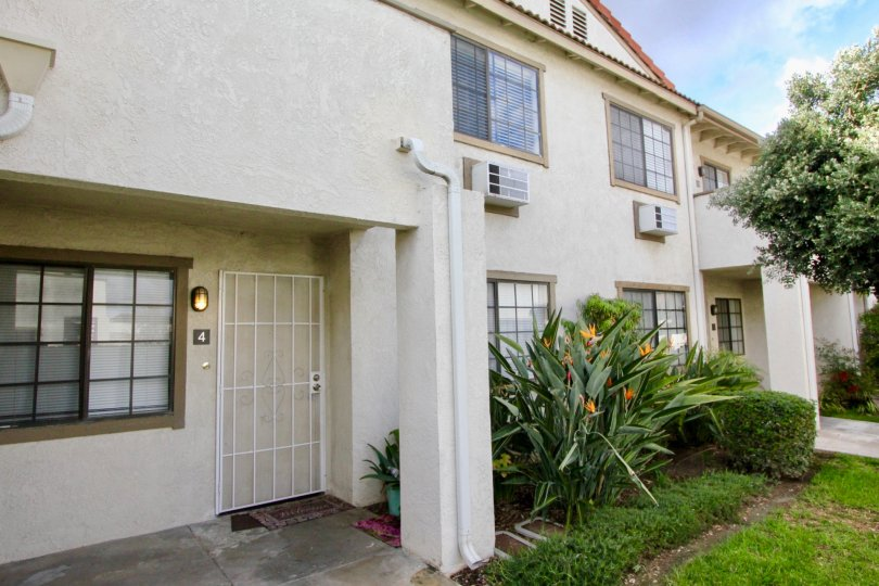 THIS IMAGE VIEWS THE SIDE VIEW OF VILLAS THAT HAS THE BEAUTIFUL LAWN, PLANTS, TREES ARE LOCATED IN THE CITY OF GARDEN GROVE