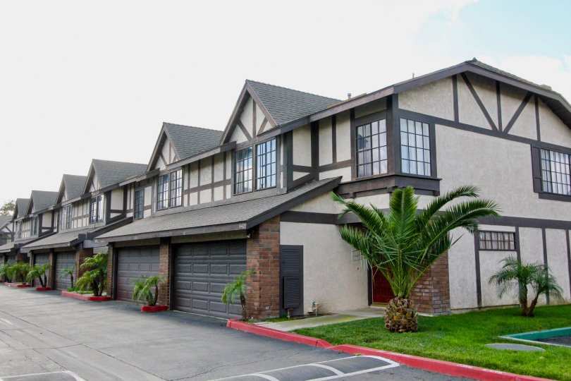 A set of Northern-European style homes with double garages and palm trees located in the Tudor Estates community in Garden Grove, California.