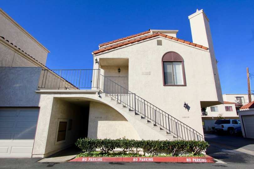 THE FRONTVIEW OF HOME WITH STEPS, CAR, PLANTS UNDER THE STEPS, ROADWAY ARE SHOWN IN THE CITY OF GARDEN GROVE
