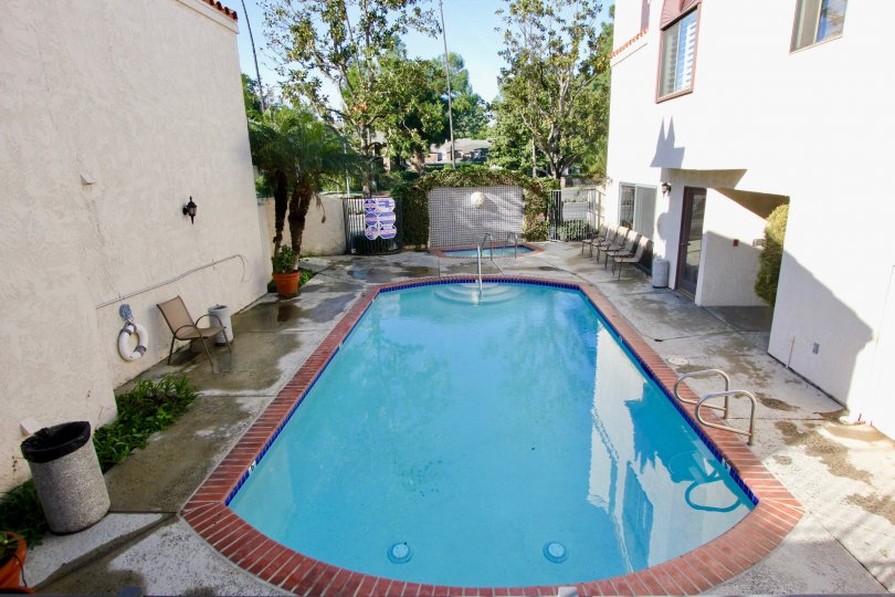 THE BACKSIDE OF THE HOUSE WITH SWIMMING POOL AND SHOWS THE LOT OF TREES PLANTS WHICH IS LOCATED IN THE CITY OF GARDEN GROVE