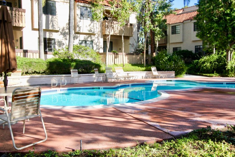 A shaded area showing a clear pool in a hotel located in the Village Green community of Garden Grove California.