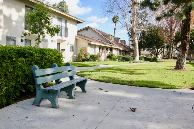 THIS IMAGE REPRESENTS APARTMENTS WHICH HAS THE BEAUTIFUL LAWN, LOT OF TREES, PLANTS WITH FLOWERS ARE SHOWN IN THE CITY OF GARDEN GROVE