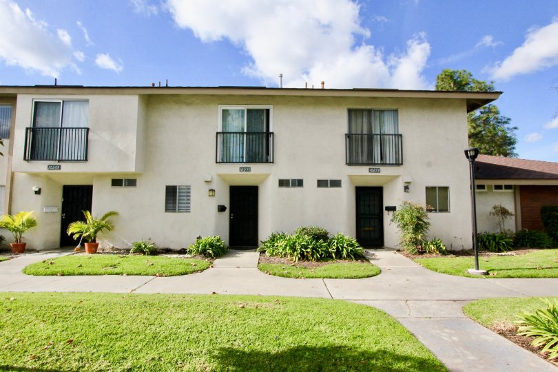Three doors to a cream colored apartment building in Westbrook, found in Garden Grove, California