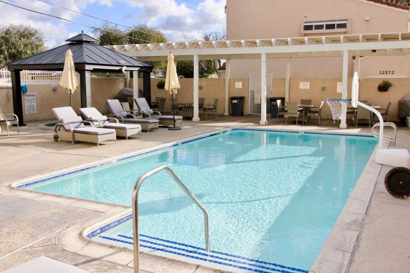 THIS IMAGE REPRESENTS THE BEAUTIFUL SWIMMINGPOOL IS IN THE GARDEN GROVE THAT HAS THE LOT OF CHAIRS, TABLES AND NUMBER BOARD