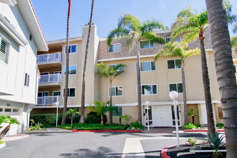 A four story condominium structure with many windows sits behind a driveway at Bayport in Huntington Beach CA