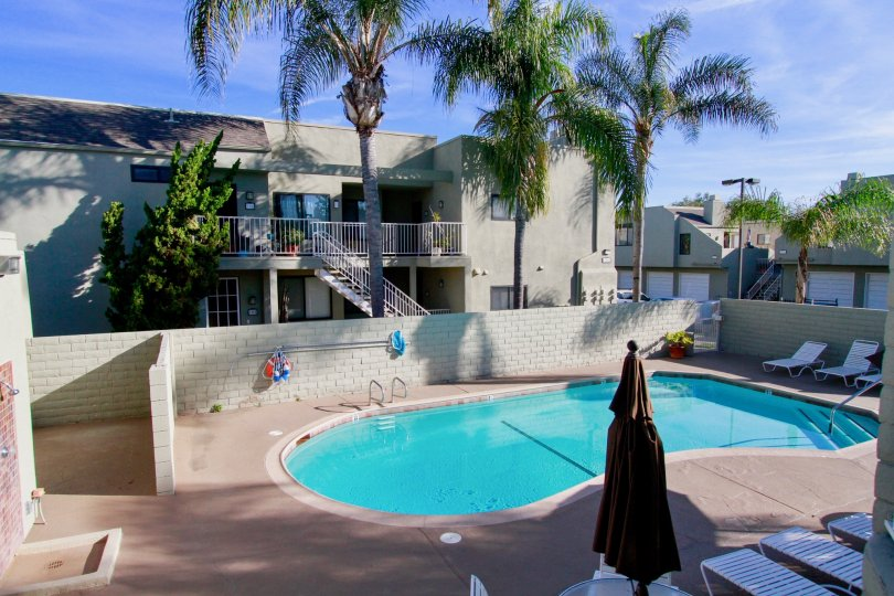 BrookstoneHuntington Beach California bulding center place round shape swmming pool blue color water near to stepesback side three palm tree and balcony and steps same home color light gray
