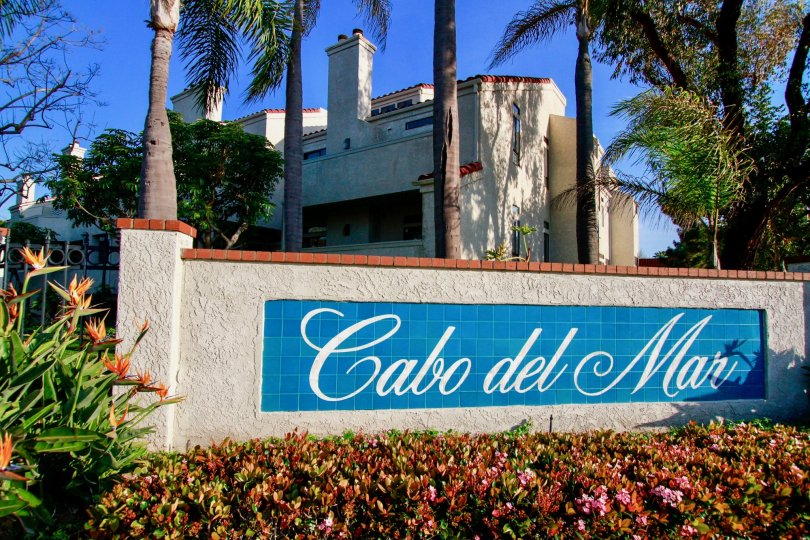 THE BOARD OF SIGN REPRESENTS CABO DEL MAR AND MORE FLOWERS ARE IN FRONT OF THE BOARD AND A BUILDING BACKSIDE OF THE SIGN AND SOME TREES ALSO AVAILABLE.