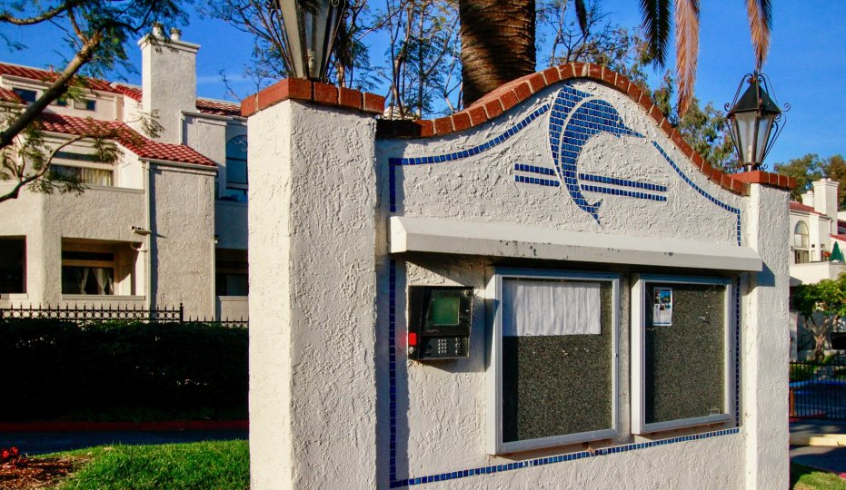 The keypad entrance to the Cabo Del Mar community. There is a tile dolphin on the keypad entrance.