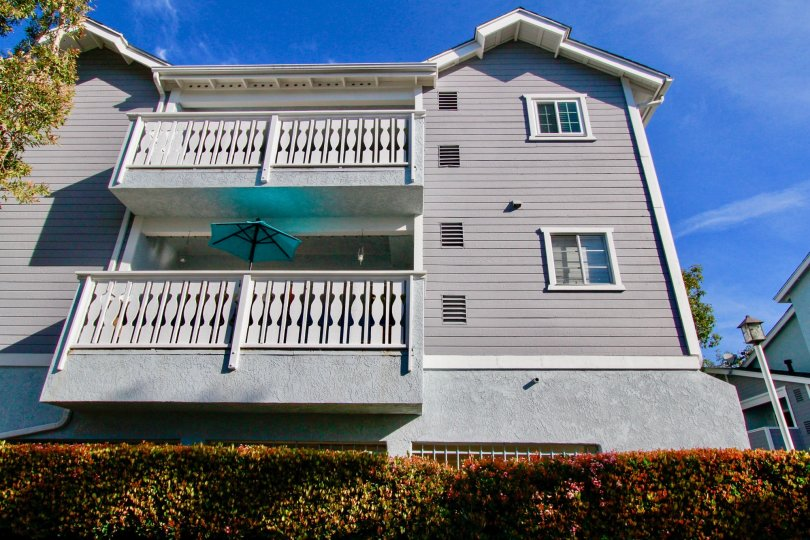A three story town home with large balcony towers above a green hedge inside Capewoods in Huntington Beach CA