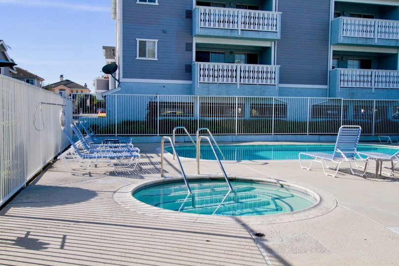 Capewoods pool and hot tub with a fence and deck chairs on a sunny day.