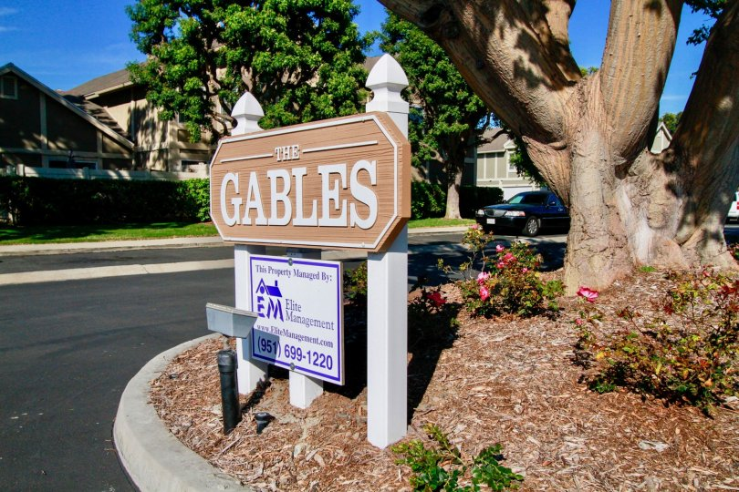 Gables sign with a lamp and a trees around it on a sunny day.