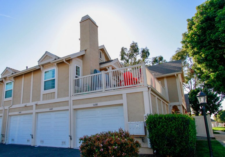 Excellent view of a villa with sunshine and terrace place with trees around in Gables of Huntington Beach
