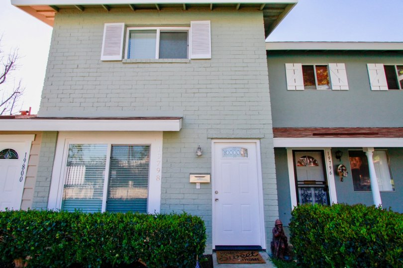 Huntington Continental Huntington Beach California building light gray color paint front glass window attached white color door attached