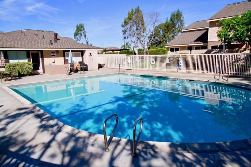 Blue coloured swimming pool between villas in Huntington Cove of Huntington Beach