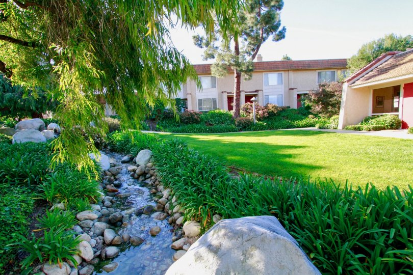Excellent greenary with lawn and water pond in front of villas in Huntington Creek of Huntington Beach, CA