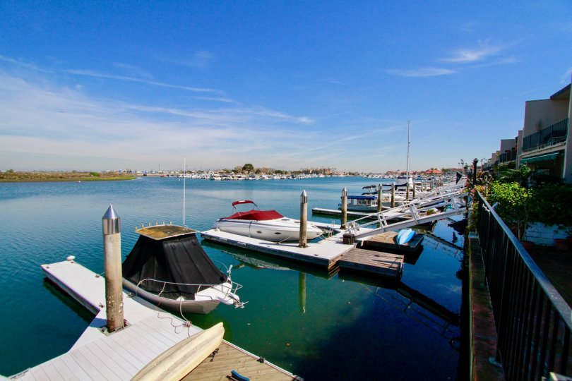 Boats of the Huntington Marina with docks and a fence on a sunny day.