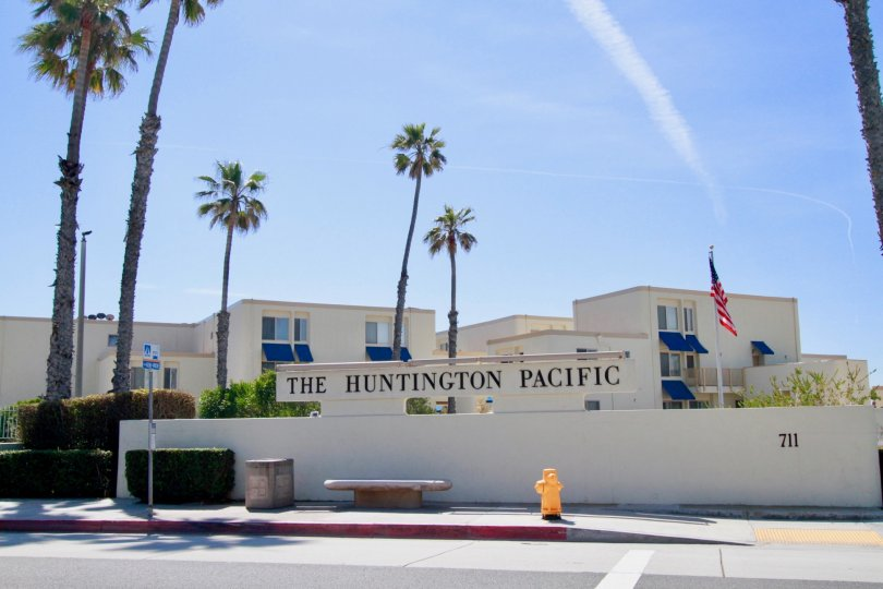 Huntington Pacific sign with a fence and palm trees on a sunny day.