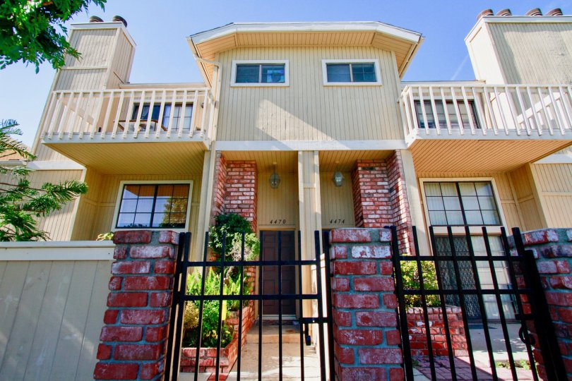 A red brick and iron gate entrance to the Huntington Terrace community townhomes.
