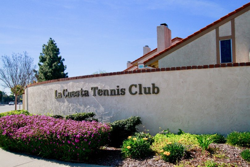 La Cuesta Tennis Club sign with flowers and bushes on a sunny day.