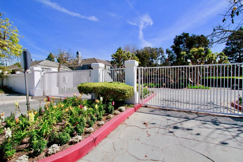 Pacific Ranch Townhomes gate with flowers and bushes in front of it.