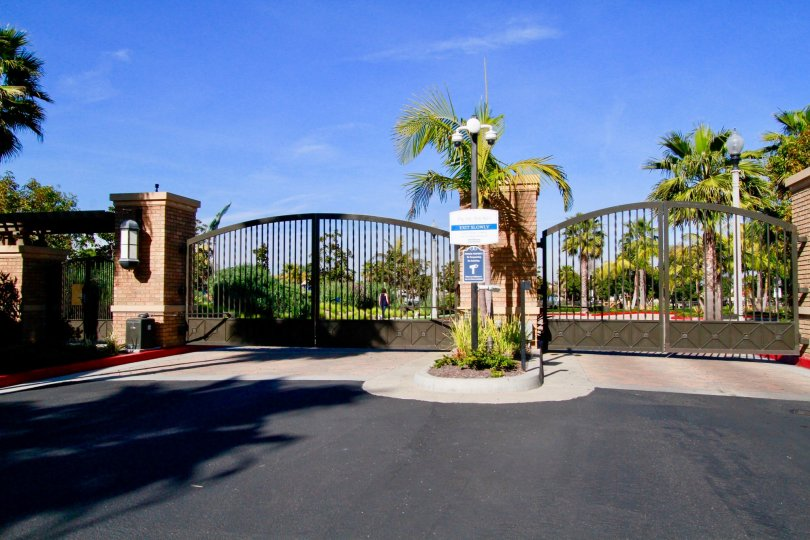 The front portion of the building in the Pacific Shores with big gates and palm trees, shrubs and camera.